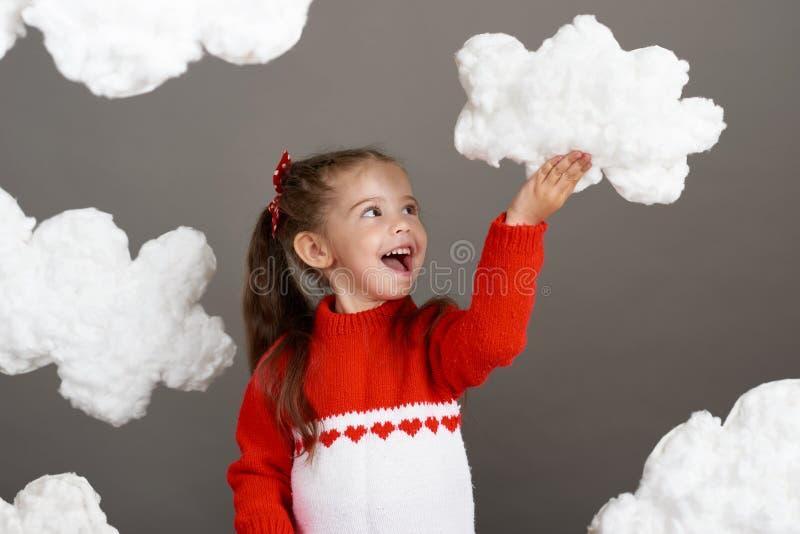 使用与云彩的女孩,穿戴在红色毛线衣,射击在灰色背景的演播室 免版税库存图片