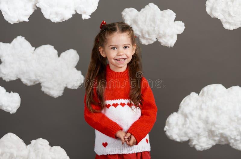 使用与云彩的女孩,穿戴在红色毛线衣,射击在灰色背景的演播室 库存图片