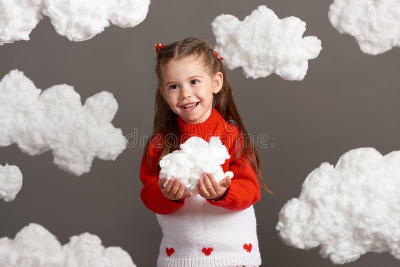 使用与云彩的女孩,穿戴在红色毛线衣,射击在灰色背景的演播室 免版税库存照片