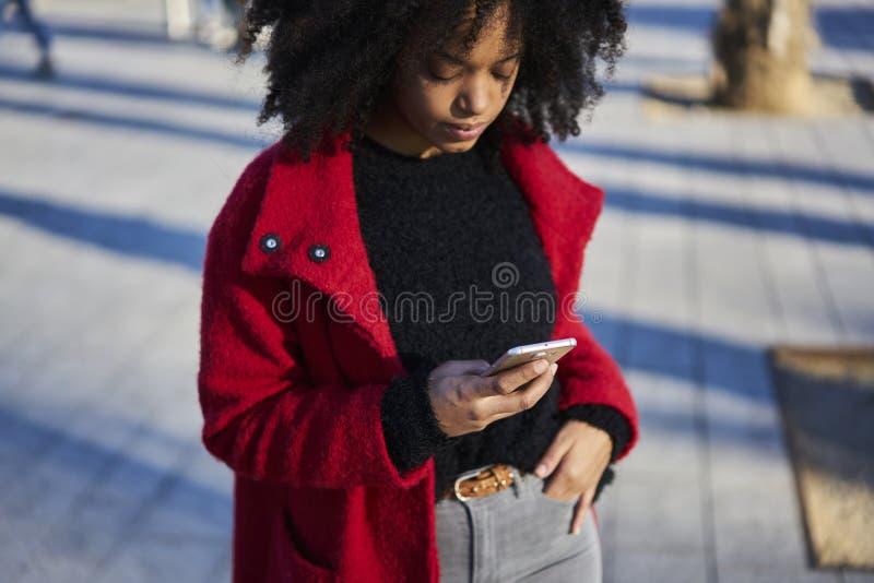 使用与互联网和现代智能手机的迷人的快乐的非裔美国人的妇女无线连接 库存照片