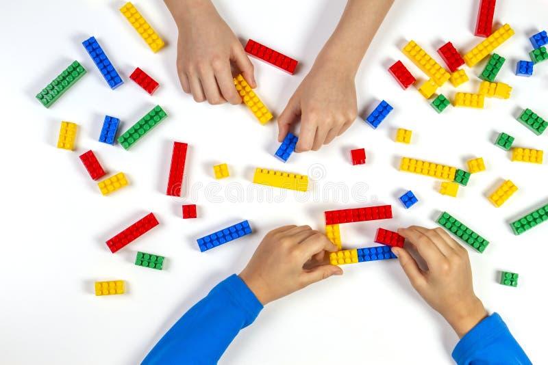 使用与五颜六色的在白色背景的大厦塑料砖的孩子手 教育开发的玩具背景 图库摄影