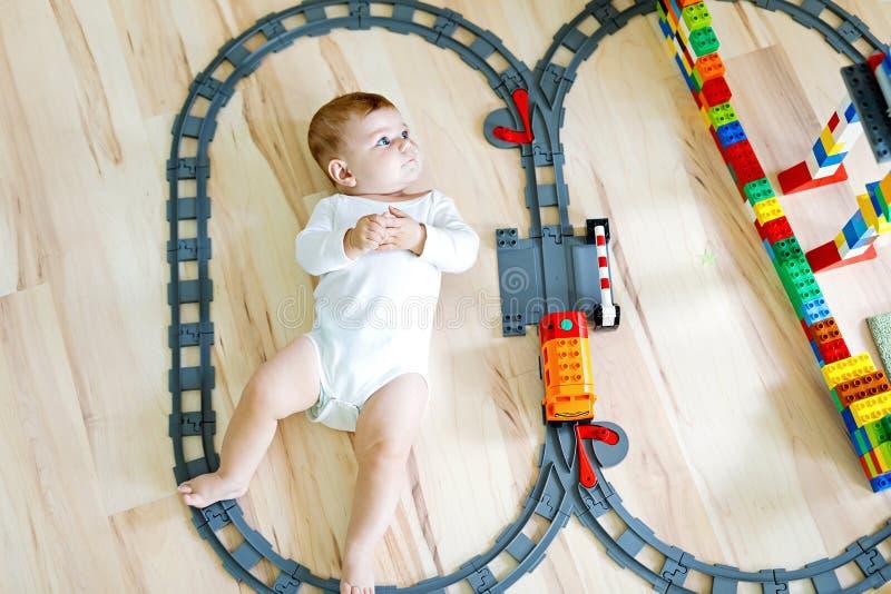 使用与五颜六色的塑料块和创造火车站的可爱的矮小的女婴 库存图片