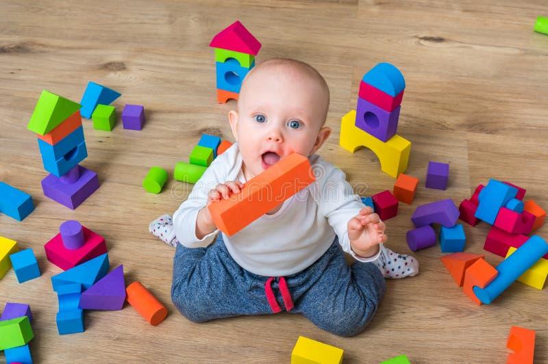使用与五颜六色的玩具块的逗人喜爱的矮小的女婴 免版税图库摄影