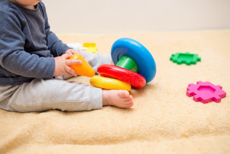 使用与五颜六色的玩具金字塔的可爱宝贝在轻的卧室 小孩的玩具 有教育玩具的孩子 o 免版税图库摄影