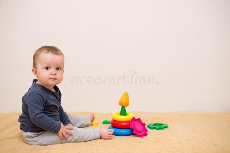 使用与五颜六色的玩具金字塔的可爱宝贝在轻的卧室 有教育玩具的孩子 o 与拷贝的背景 免版税库存图片