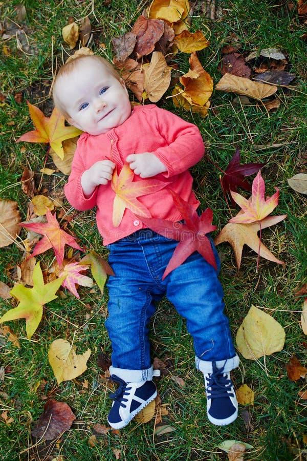 使用与五颜六色的秋叶的女婴户外 免版税库存照片