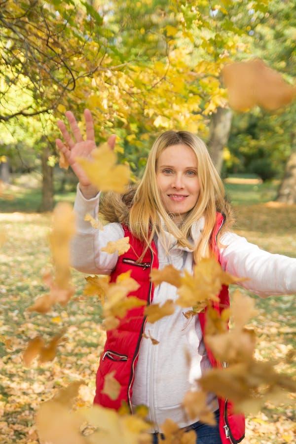 使用与五颜六色的秋天叶子的妇女 免版税库存照片