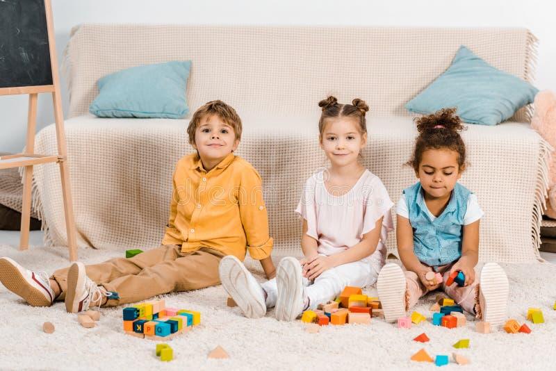 使用与五颜六色的立方体和微笑的可爱的不同种族的孩子 图库摄影
