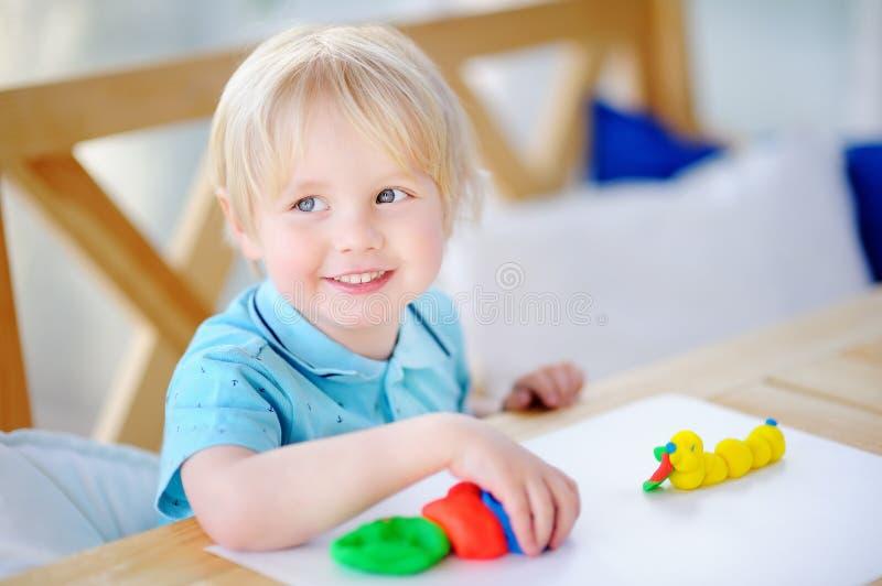 使用与五颜六色的雕塑黏土的创造性的男孩在幼儿园 图库摄影