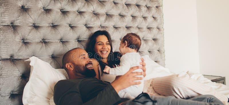 使用与他们在床上的新出生的儿子的愉快的父母 库存图片