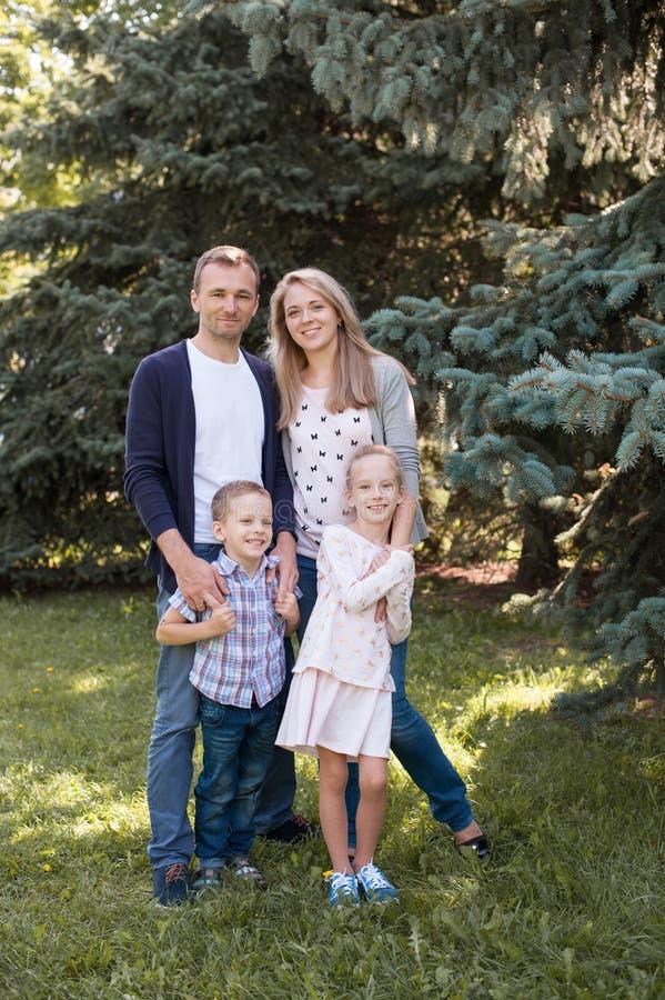 使用与他们英俊的儿子和女儿的妈妈和爸爸-户外家庭和孩子在公园-年轻美丽 免版税库存照片