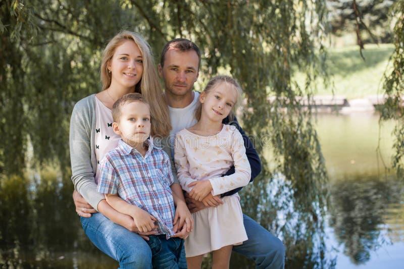使用与他们英俊的儿子和女儿的妈妈和爸爸-户外家庭和孩子在公园-年轻美丽 免版税图库摄影