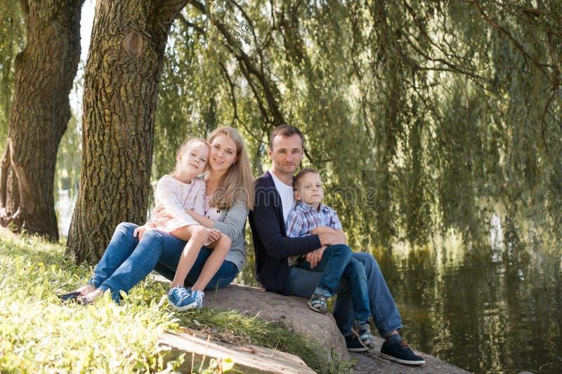 使用与他们英俊的儿子和女儿的妈妈和爸爸-户外家庭和孩子在公园-年轻美丽 库存照片