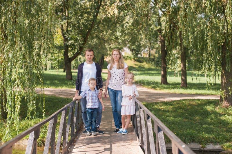 使用与他们英俊的儿子和女儿的妈妈和爸爸-户外家庭和孩子在公园-年轻美丽 库存图片
