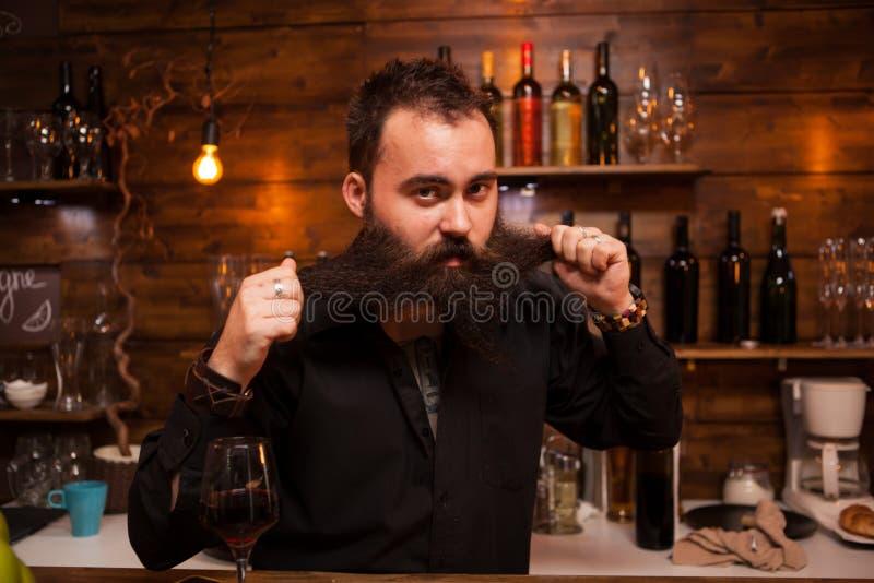 使用与他在柜台后的长的胡子的可爱的侍酒者 免版税库存照片