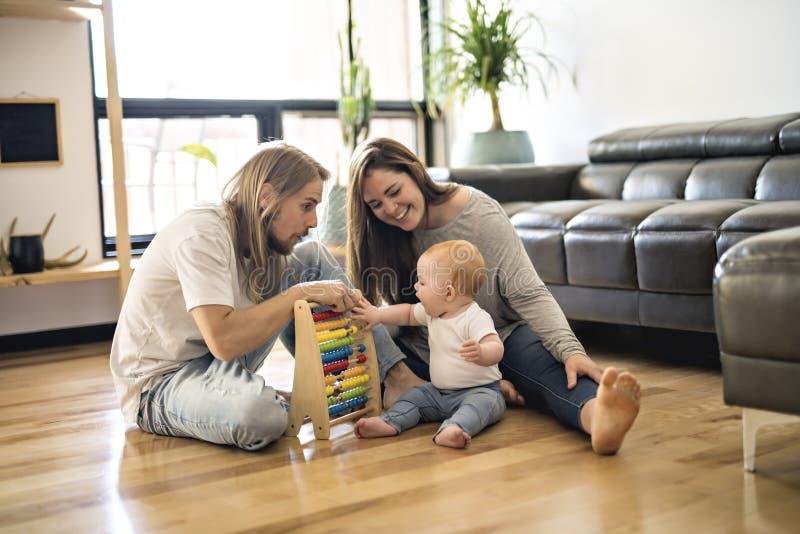 使用与他的在地板上的女婴的快乐的父母在客厅 图库摄影