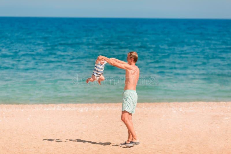 使用与他的婴孩的年轻愉快的父亲在海滩 免版税图库摄影