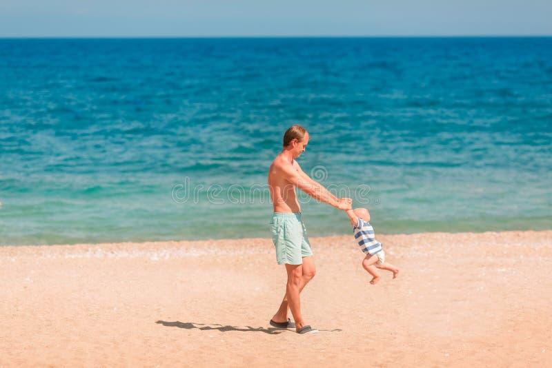 使用与他的婴孩的年轻愉快的父亲在海滩 图库摄影