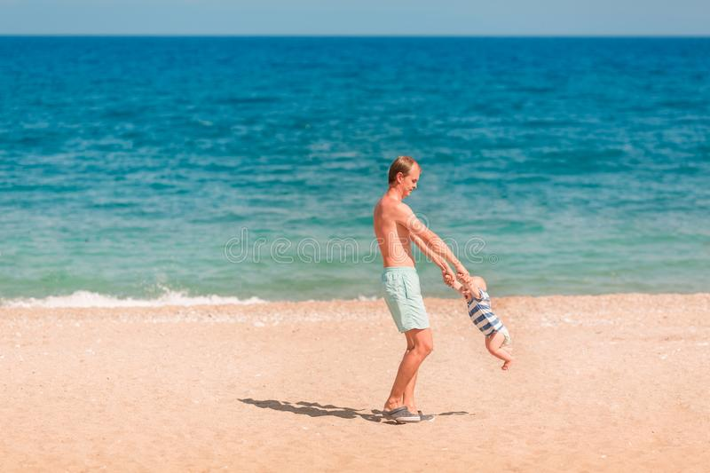 使用与他的婴孩的年轻愉快的父亲在海滩 免版税库存照片