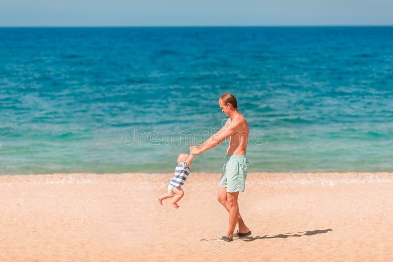 使用与他的婴孩的年轻愉快的父亲在海滩 库存图片