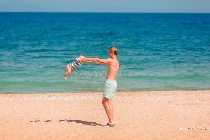 使用与他的婴孩的年轻愉快的父亲在海滩 库存照片