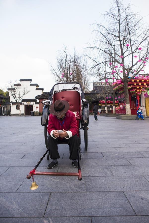 使用与他的电话等待的顾客的一个人力车人 库存照片