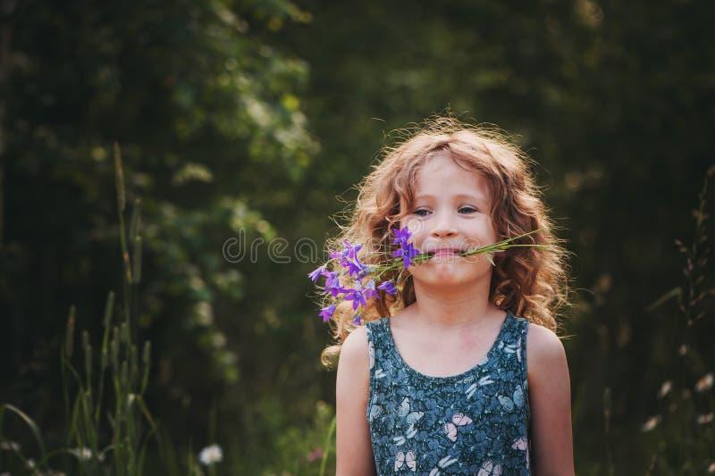 使用与会开蓝色钟形花的草花束的愉快的儿童女孩在夏天 免版税库存照片