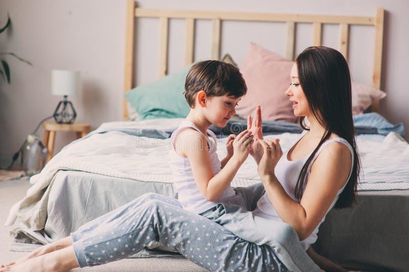 使用与儿童儿子的母亲在卧室 幸福家庭佩带的睡衣 免版税库存照片