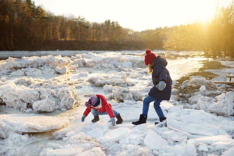 使用与冰块的两个愉快的姐妹由冻河在冰期间打破 孩子获得乐趣在冬天 库存照片
