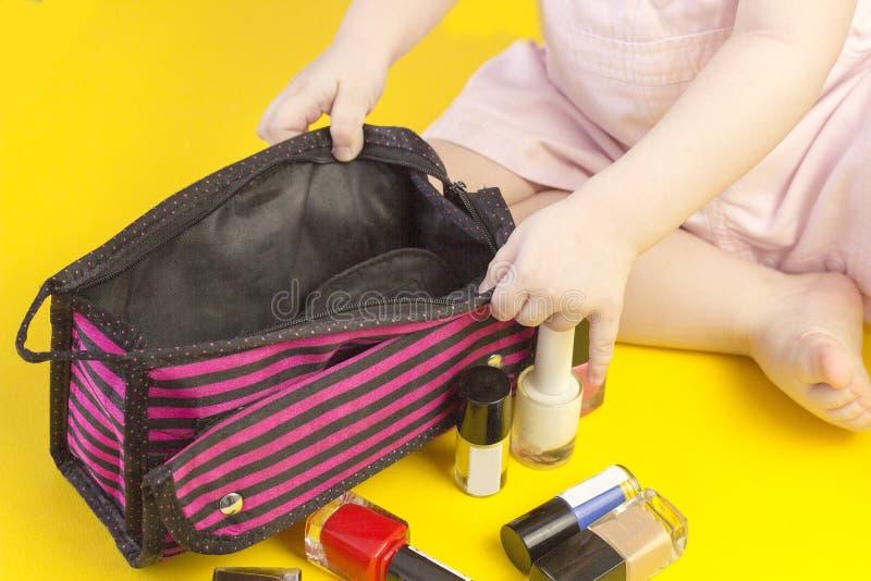 使用与化妆袋子和指甲油,黄色背景化妆用品的小女孩 库存图片
