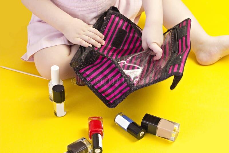 使用与化妆袋子和指甲油,黄色背景,化妆用品的小女孩 库存照片
