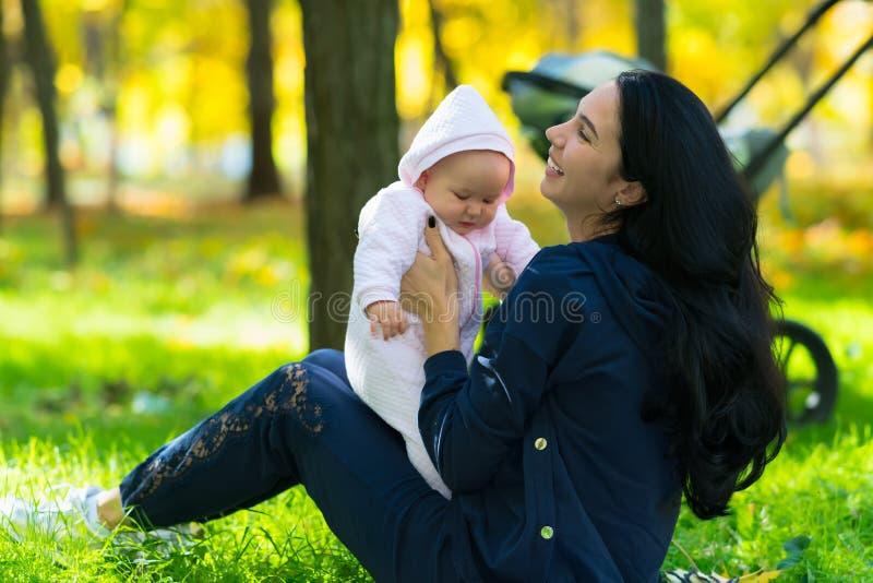 使用与可爱宝贝女孩的愉快的年轻妈咪 免版税图库摄影