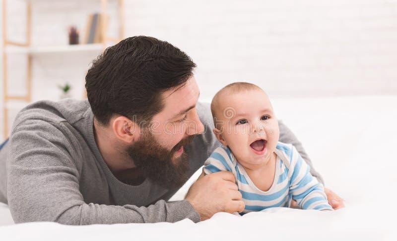 使用与可爱的婴孩的愉快的父亲在卧室 免版税库存图片