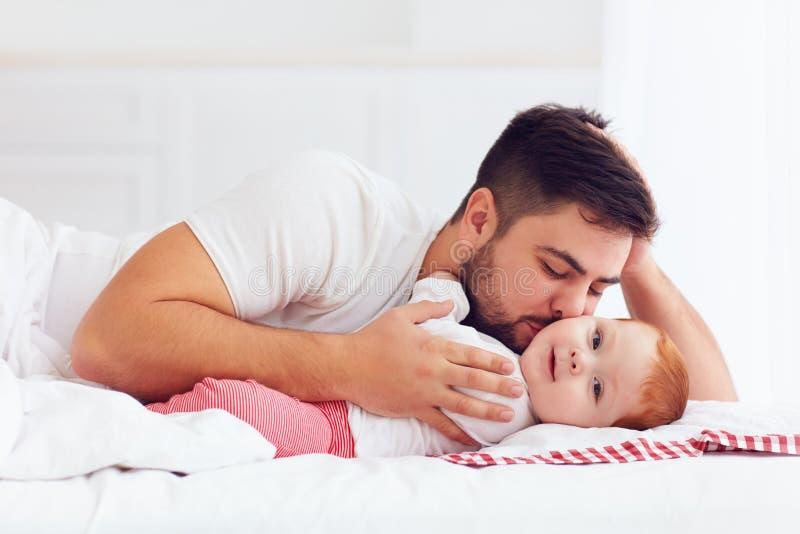 使用与可爱的婴孩的愉快的父亲在卧室 免版税库存照片