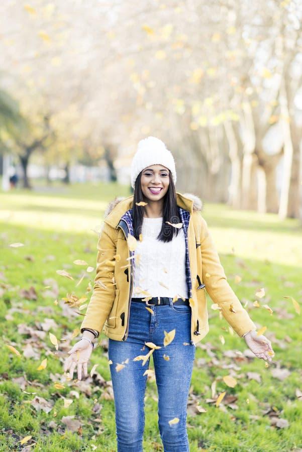 使用与叶子在公园,秋天概念的微笑的妇女 库存图片
