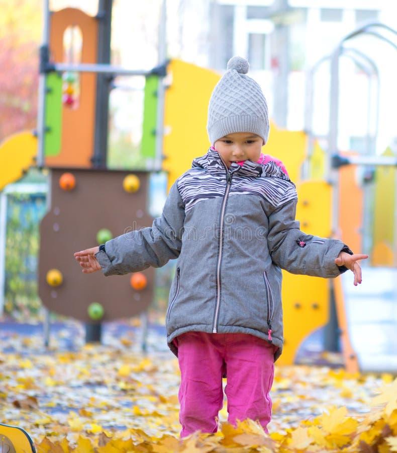使用与叶子的女孩在秋天 免版税库存图片