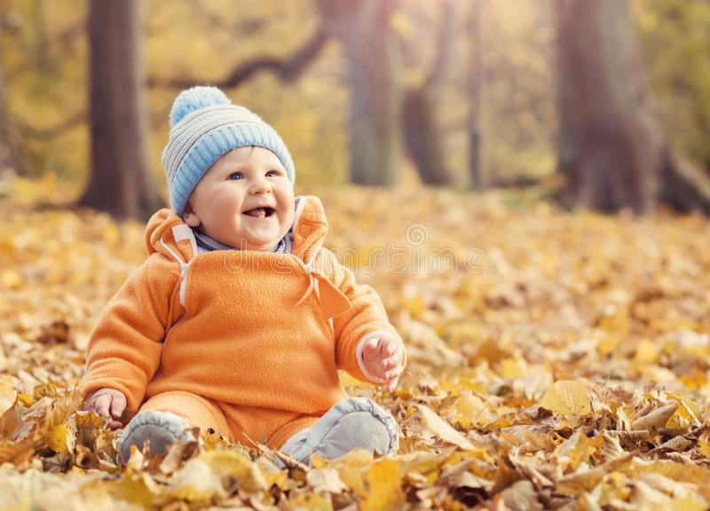 使用与叶子的愉快的小孩婴孩在秋天公园 免版税图库摄影