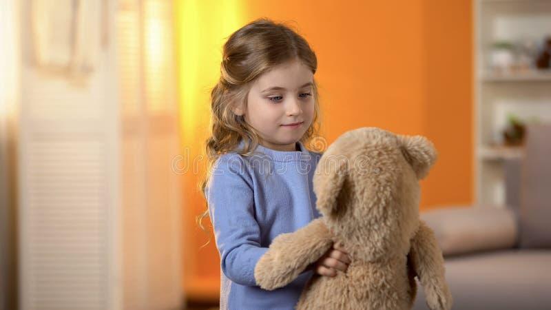 使用与喜爱的玩具熊,童年的愉快的白肤金发的卷发的女孩 免版税库存图片