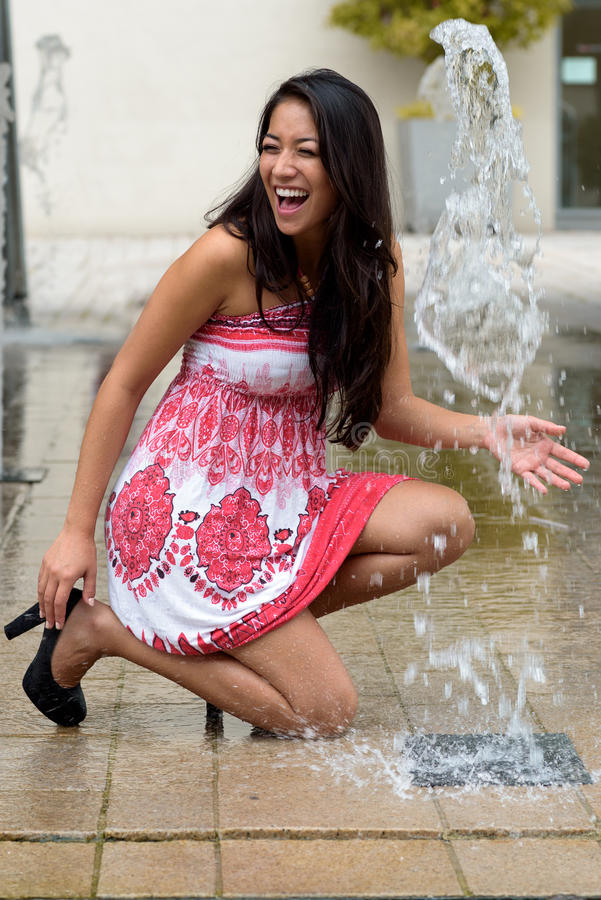 使用与喷泉的嬉戏的时髦少妇 免版税图库摄影