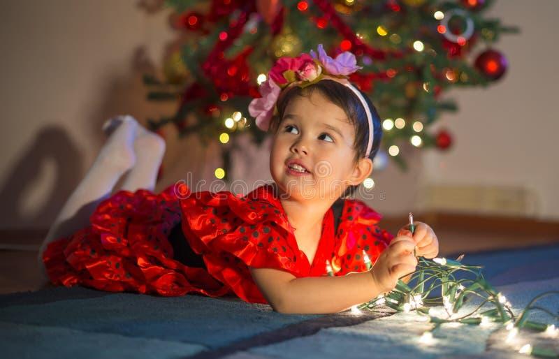 使用与圣诞灯的可爱的小女孩在树附近 免版税库存照片