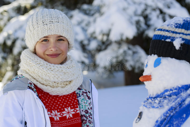 使用与在一次多雪的胜利的一个雪人的愉快的微笑的十几岁的女孩 免版税图库摄影
