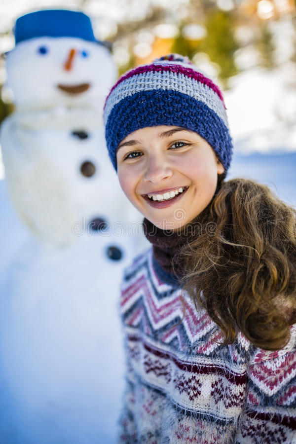 使用与在一次多雪的胜利的一个雪人的愉快的微笑的十几岁的女孩 免版税库存照片