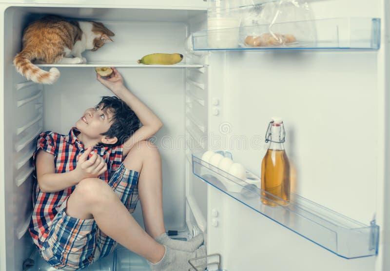 使用与在冰箱里面的红色猫的衬衣和短裤的一个男孩 图库摄影