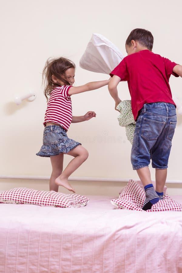 使用与在卧室的枕头的滑稽的孩子 被即兴创作的儿童争斗 库存图片