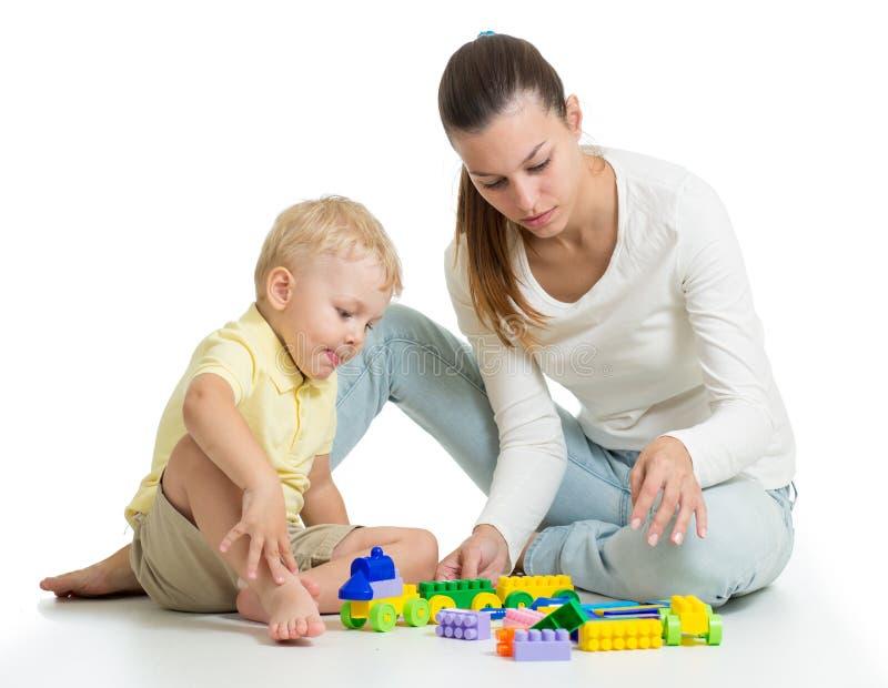 使用与在地板上的五颜六色的块玩具的孩子,隔绝在白色 母亲帮助给儿子 库存照片