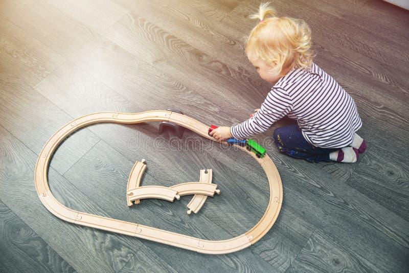 使用与在地板上的木铁路的小女孩 免版税库存图片