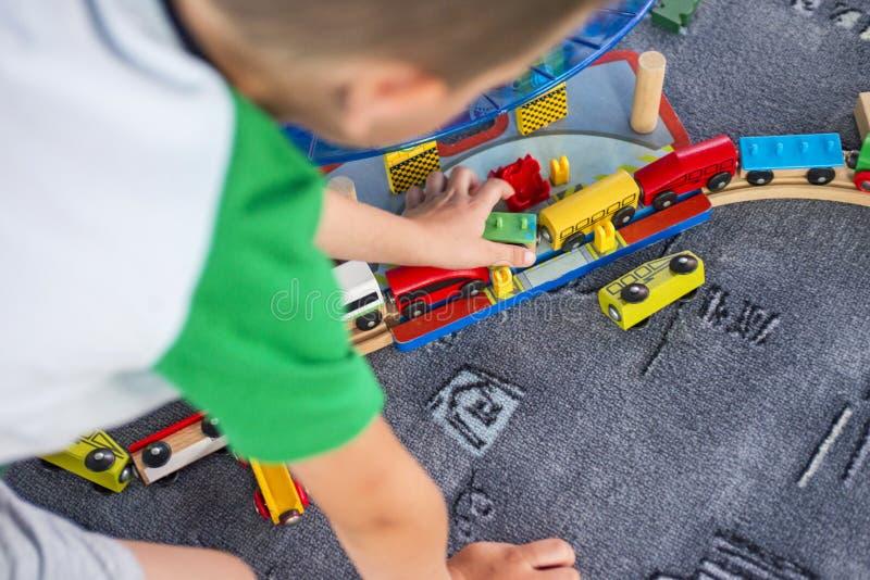 使用与在地板上的木铁路的小孩 使用与木火车集合的小男孩 库存图片