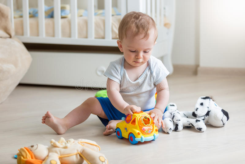 使用与在地板上的玩具汽车的可爱的男婴在客厅 库存照片