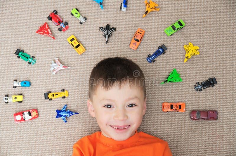 使用与在地毯的汽车汇集的愉快的男孩 孩子的,微型模型运输、飞机、飞机和直升机玩具 免版税图库摄影