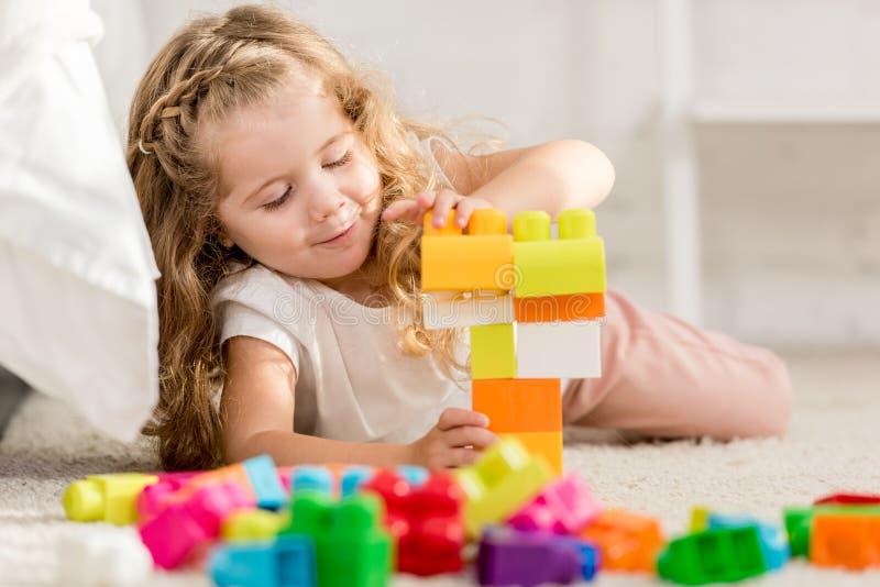 使用与在地毯的色的塑料建设者的可爱的孩子 库存照片
